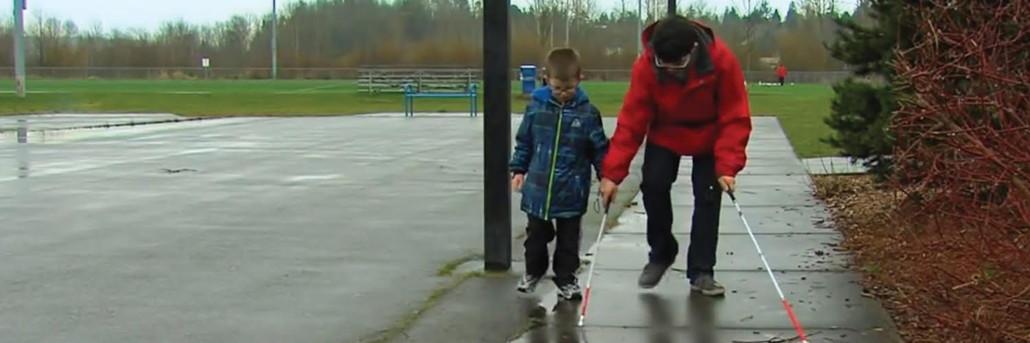 a photo of two brothers (Conner and Dalton McKittrick) wearing glasses, rain coats and pants. The boys are walking on a sidewalk, looking down at the ground while using the older brother shows his younger brother how to use a white and red guide cane. Both boys are using a white and red guide canes.